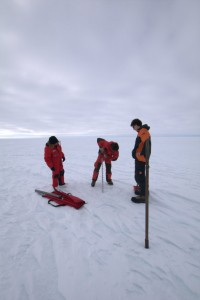 A familiar picture — sea ice researchers standing around watching some else drill with a kovacs ice thickness drill.