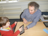 A child chooses icons to 'speak' with Professor Jeff Sigafoos
