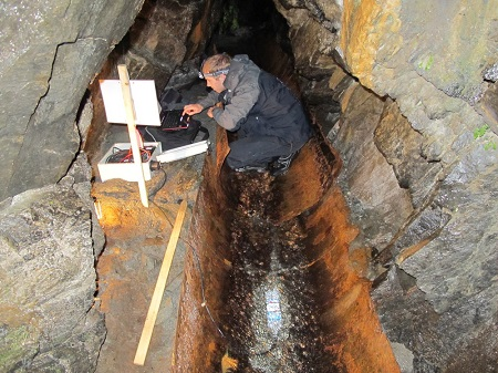 Figure 2. University of Otago student Alex Sims monitors flow of groundwater through Tartare Tunnels near Franz Josef.