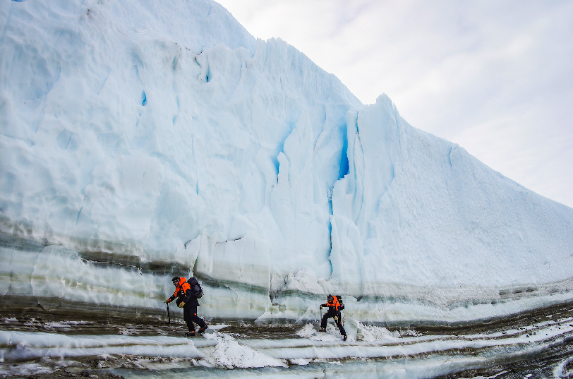 Two scientists on reconnaissance for a potential ice core sampling site. Although there is debris at the foot of the ice cliff, ice fall is very rare at the cold-based glaciers of the McMurdo Dry Valleys and especially in the early morning, when temperatures are low and even from the cold of the night.