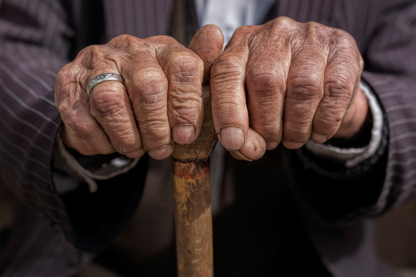 Ageing hands holding a cane